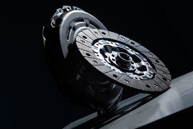 Close-up picture of a part of car, black clutch disk isolated on black background