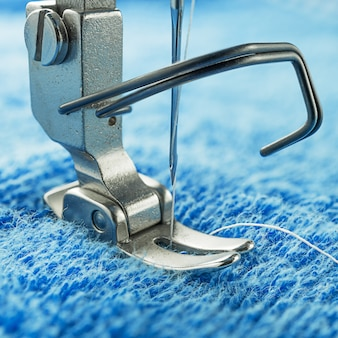 Close up picture of sewing machine parts  needle and presser foot on blue fabric