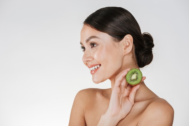 Close up picture of smiling woman with healthy fresh skin holding kiwi and looking aside, isolated over white
