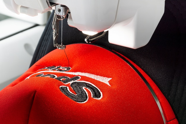Close up picture of sport cap and embroidery machine