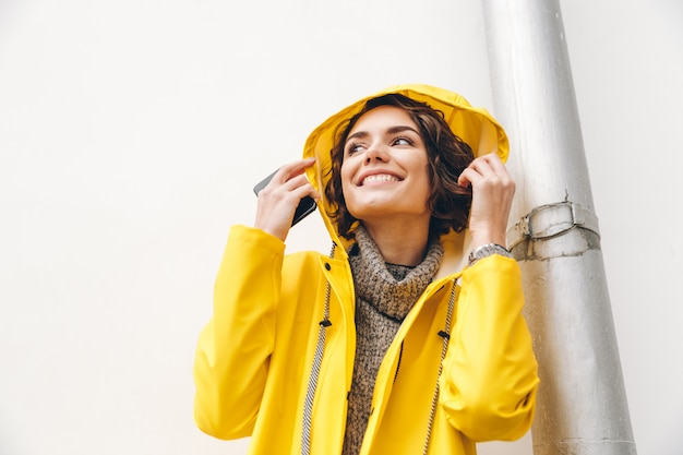 Close up picture of stylish female in yellow coat wearing hood on and enjoying rainy weather while walking outdoors