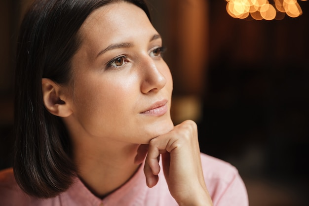 Close up picture of thoughtful brunette woman