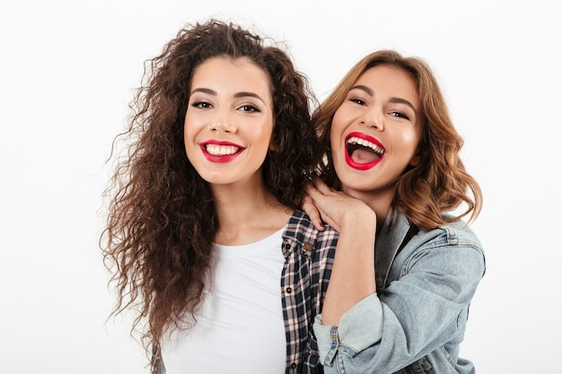 Close up picture of two cheerful girls posing together  over white wall