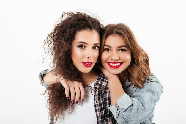 Close up picture of two smiling girls posing together  over white wall