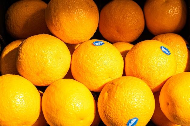 Крупным планом изображение с большим количеством свежих апельсинов и красных грейпфрутов на солнце.