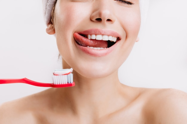 Ritratto del primo piano della donna che anticipa la spazzolatura dei denti. modello con sorriso bianco come la neve in posa sul muro bianco.