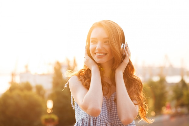 Close up picture of young beauty ginger woman in dress listening music on the sunset