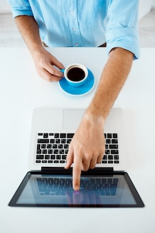 Close up picture of young businessman's hands sitting at table pointing on laptop screen holding coffee cup. white modern office interior