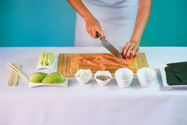 Close up picture of young lady's hands slicing salmon