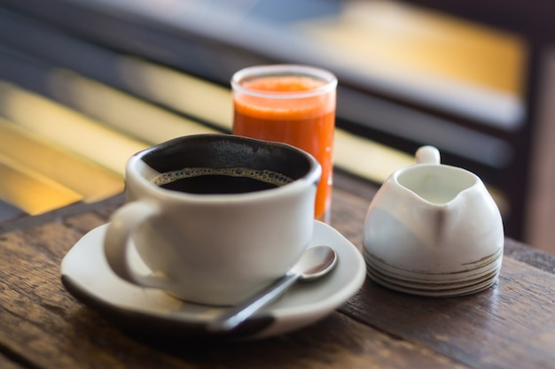 モーニングコーヒーとヘルシーキャロットジュース、オーガニックヘルシーカフェ、手作りのおしゃれな料理の写真を閉じます。