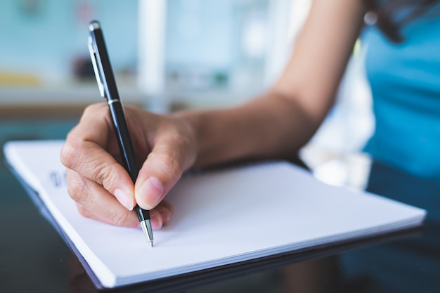 Close-up pictures of women using a black pen to write on a blank notebook on a glass table