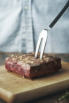 Close up piece of grilled meat on wooden board with steel big fork in it