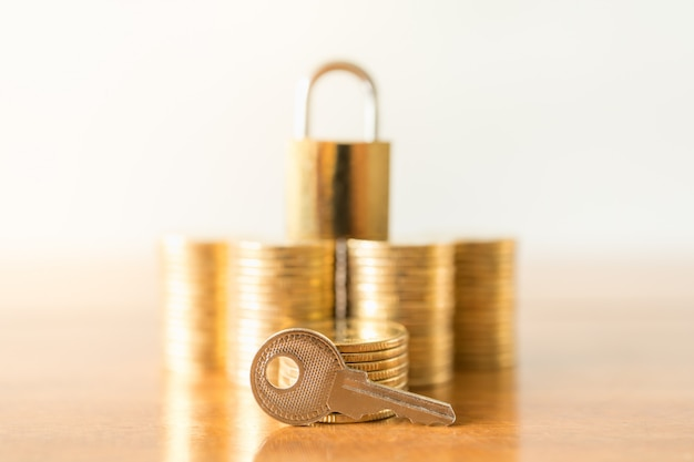 Close up of piece key with stack of gold coins and master key lock on wooden table with copy space.