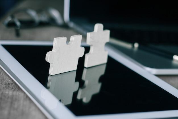 Крупный план. кусок пазла на экране планшета на рабочем столе