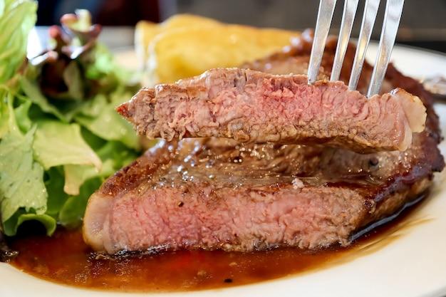 Крупный план, нарезанный вилкой филе говядины с коричневым соусом.