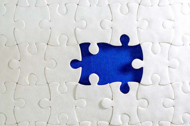 Close up piece of the white jigsaw puzzle , concept of business challenge completion with teamwork