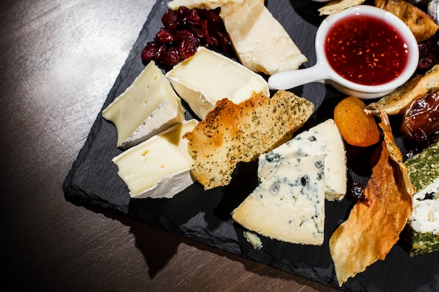 Close-up of pieces of blue cheese and camembert lying on black plate