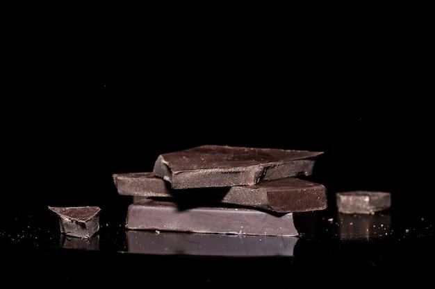 Кусочки черного горького шоколада крупным планом, лежащие на зеркальной поверхности, изолированной на черном