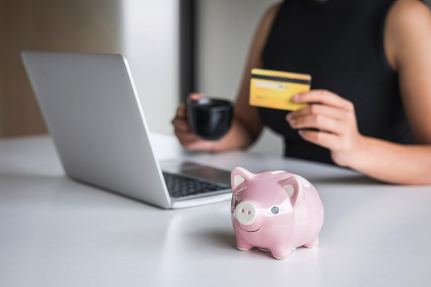 Close up of piggy bank, business woman consumer holding credit card and typing on laptop for online shopping and payment make a purchase on the internet, online payment, networking and buy product