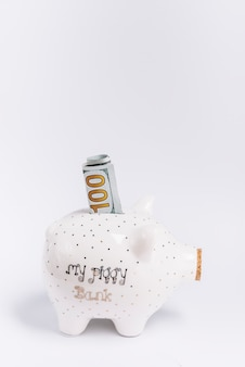 Close-up of piggybank with hundred banknote on white backdrop