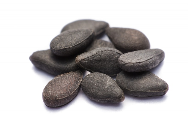 Close up pile of black sesame seeds isolated on white
