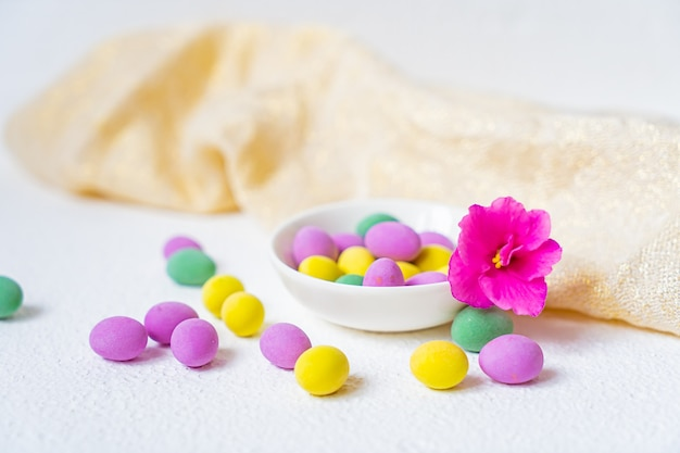 Close up of a pile of colorful chocolate easter eggs and a pink flower isolated on white background
