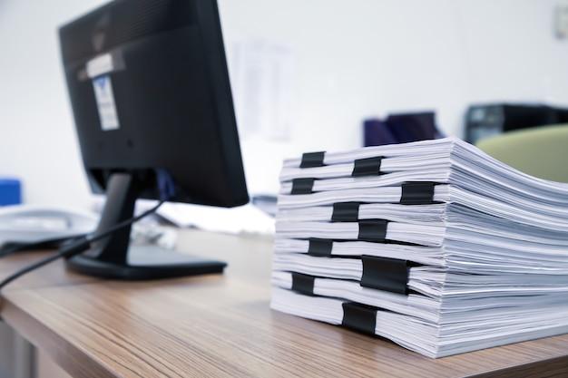 たくさんの紙と書類のレポートまたはオフィスデスクの印刷ドキュメントのクローズアップの山を積み上げます。