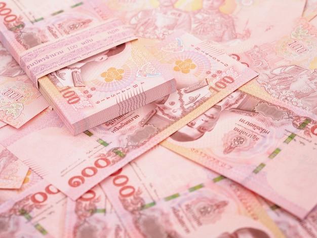 Закройте кучу тайских банкнот 100 бат на белом фоне, вид сверху.