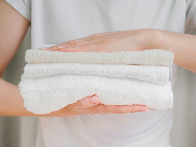 Close up pile of towels between hands
