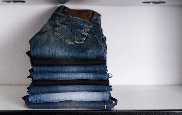 Close up piled assorted clean casual blue jeans for men displayed on white shelf