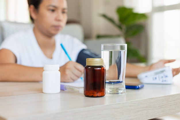 Close up on pills bottle and a glass of water while asian young woman is checking blood pressure and heart rate with digital pressure gauge by herself at home. health and medical concept.