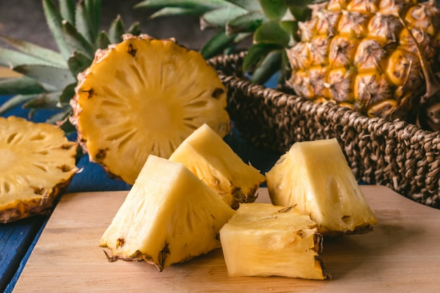 Close up of pineapple fruit with slices on wooden tray