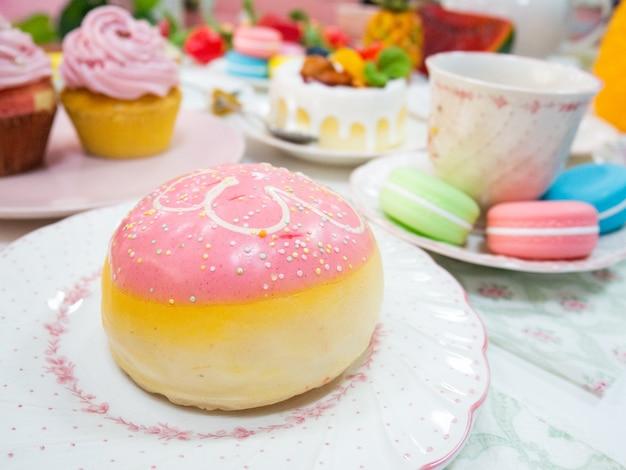 마카롱 컵케익과 찻잔 디스플레이와 함께 하얀 접시에 분홍색 인공 도넛이나 가짜 도넛을 닫습니다.
