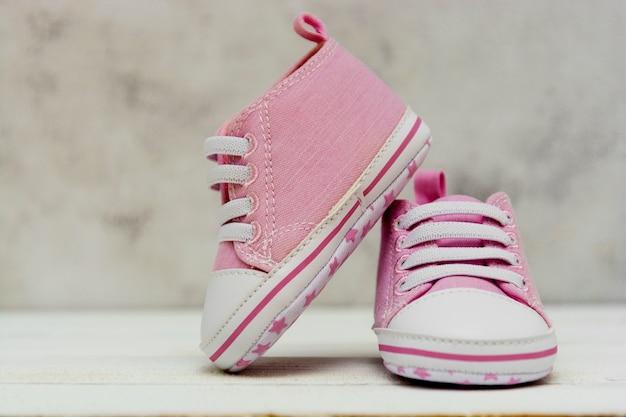 ピンクの赤ちゃんの女の子のスニーカーをクローズアップ、スポーツシューズはニューボード、母性、コピースペースと妊娠の概念を閉じます。