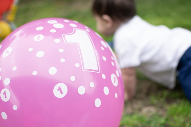 Close up pink balloon with number one on with blurred one year old baby crawling
