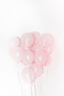 Close-up of pink balloons for birthday decoration against white backdrop