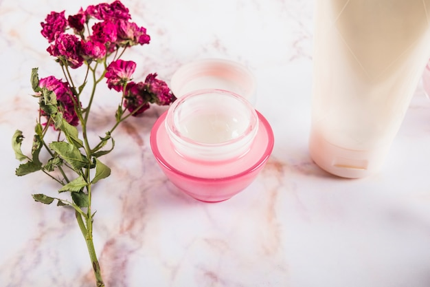 Close-up of pink flowers near skin care creams on marble