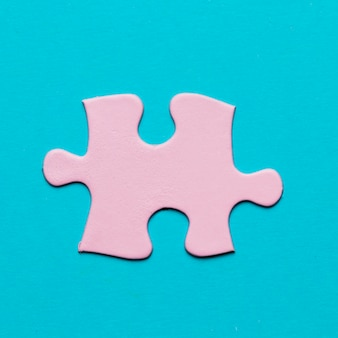 Close-up of pink jigsaw puzzle piece on blue background