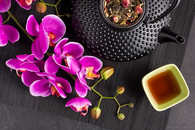 Close-up of pink orchid flower and dry herb tea on place mat
