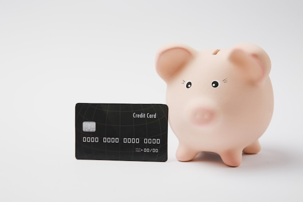 Close up of pink piggy money bank and black credit card isolated on white wall background. money accumulation, investment, banking or business services, wealth concept. copy space advertising mock up.
