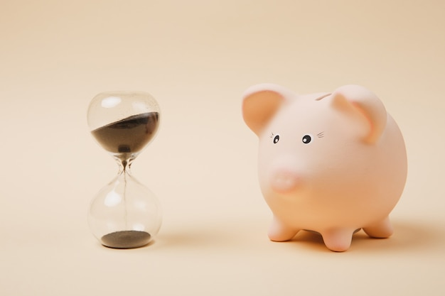 Close up of pink piggy money bank and sandglass isolated on pastel beige wall background. money accumulation, investment, banking or business services, wealth concept. copy space advertising mock up.