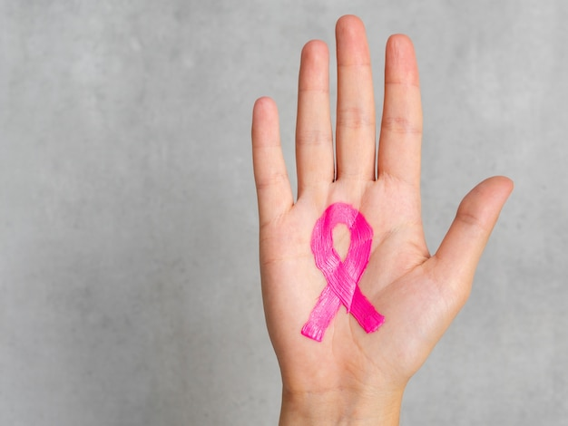 Close-up pink ribbon painted on palm
