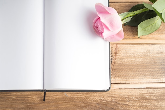 Close-up of pink rose on the blank open diary on wooden table
