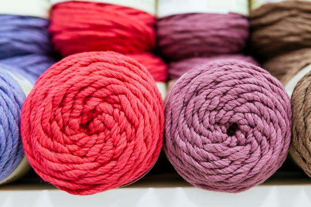 Close up of pink and ultraviolet wool yarns on a shelf