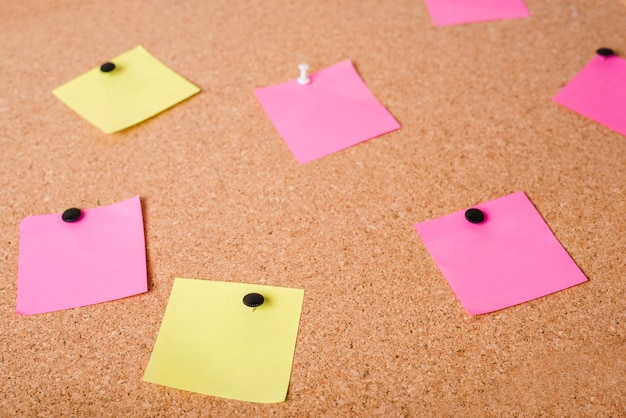 Close-up of pink and yellow adhesive notes on corkboard