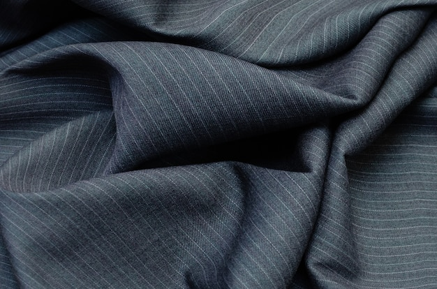 Close up of pinstriped fabric texture for garment manufacturing in dark grey color. wool textile for costume fashion.