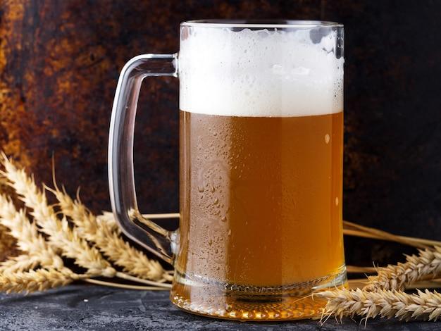 Закройте кружку нефильтрованного пшеничного пива с пеной и колосьями пшеницы