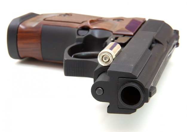 The close up of a pistol a target and cartridges is isolated