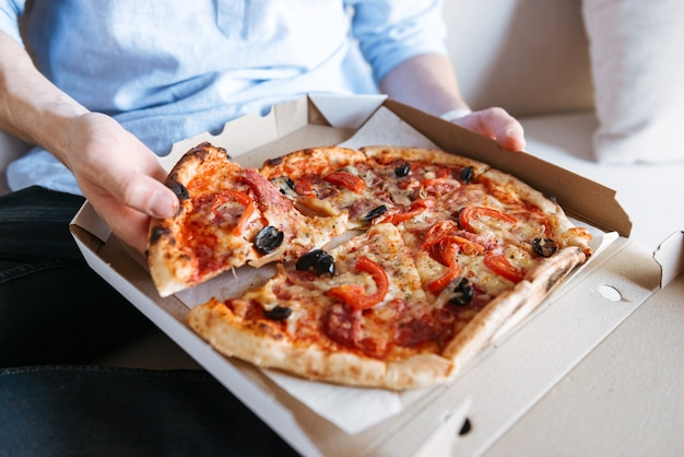 Close up of a pizza in box on men's lap