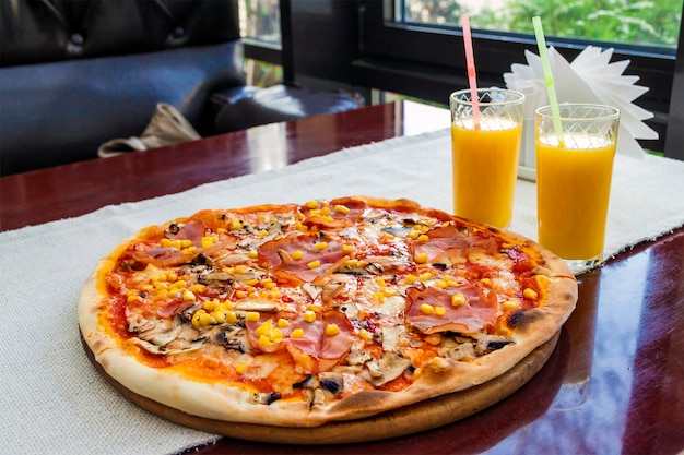 Close up of pizza with meat and corn and two glasses of orange juice